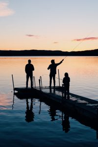 Father and Son and Brother enjoying Fishing From the Dock at Sunset