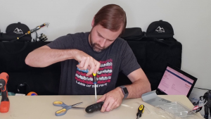 Removing the screw to the battery compartment on the Rapala Electric line remover